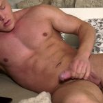young blond bodybuilder lies on the bed an masturbtes
