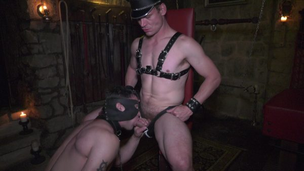 submissive guy with face mask sucks dominant master in dungeon