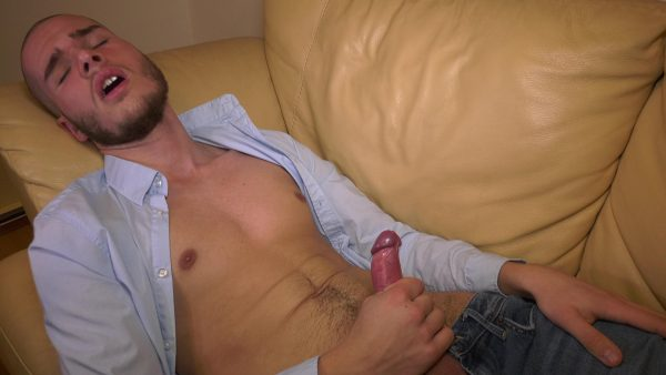 twink lies on sofa with shirt open and masturbates