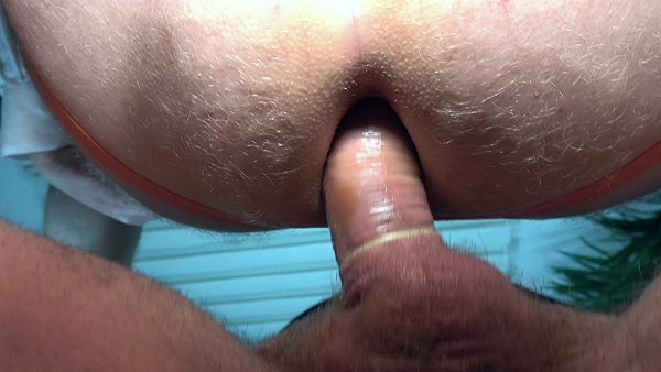 cock with condom is penetrating a hairy male ass