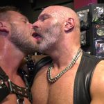 two mature muscled man in harness kiss with tongue in fetish store