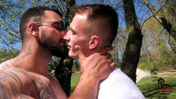 muscleman with sunglasses kisses sexy blond stud outdoors