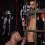 hairy stud with big cock in a cage gets sucked by muscle guy