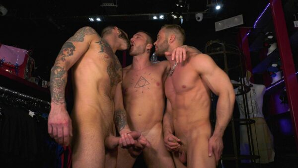 three naked studs kiss each other and jerk off in a store